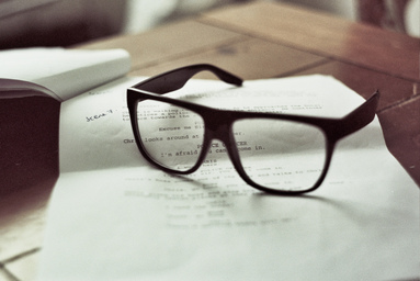 a pair of glasses sit on a script